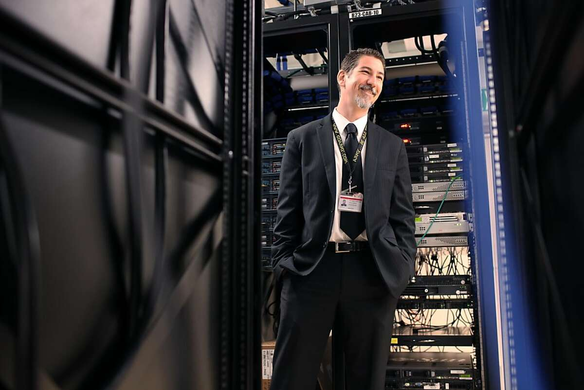 Surrounded by switch panels, electrical cords and blinking lights Erik Heinrich the Director of Infrastructure in the Information Technology Department of the San Francisco School District laughs with a coworke inside the data center at the SFUSD Headquarters in San Francisco Calif, on Wednesday, June 8, 2011.