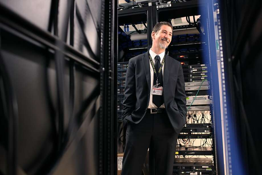 Surrounded by switch panels, electrical cords and blinking lights Erik Heinrich the Director of Infrastructure in the Information Technology Department of the San Francisco School District laughs with a coworke inside the data center at the SFUSD Headquarters in San Francisco Calif, on Wednesday, June 8, 2011. Photo: Alex Washburn, Special To The Chronicle