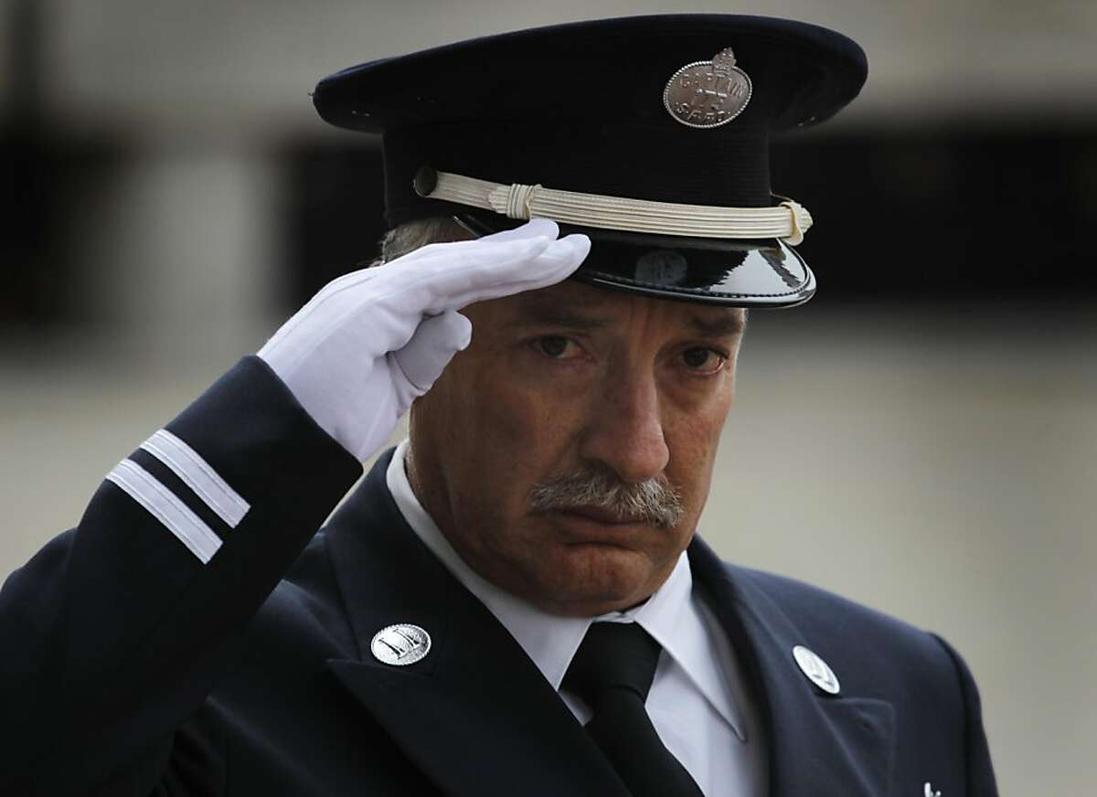 A fire department captain salutes as the bodies of firefighters Lt. VIncent Perez and Anthony Valerio arrive for a wake at Saint Mary's Cathedral in San Francisco, Calif. on Thursday, June 9, 2011. Perez and Valerio died while fighting a Diamond Heights house fire last week.