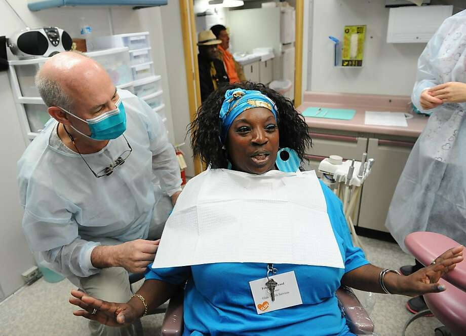 Monte Cooper provides dental service on Felecia Haywood in Glide Health Services's Toothtravelers dental van on June 16, 2011. Photo: Susana Bates, Special To The Chronicle