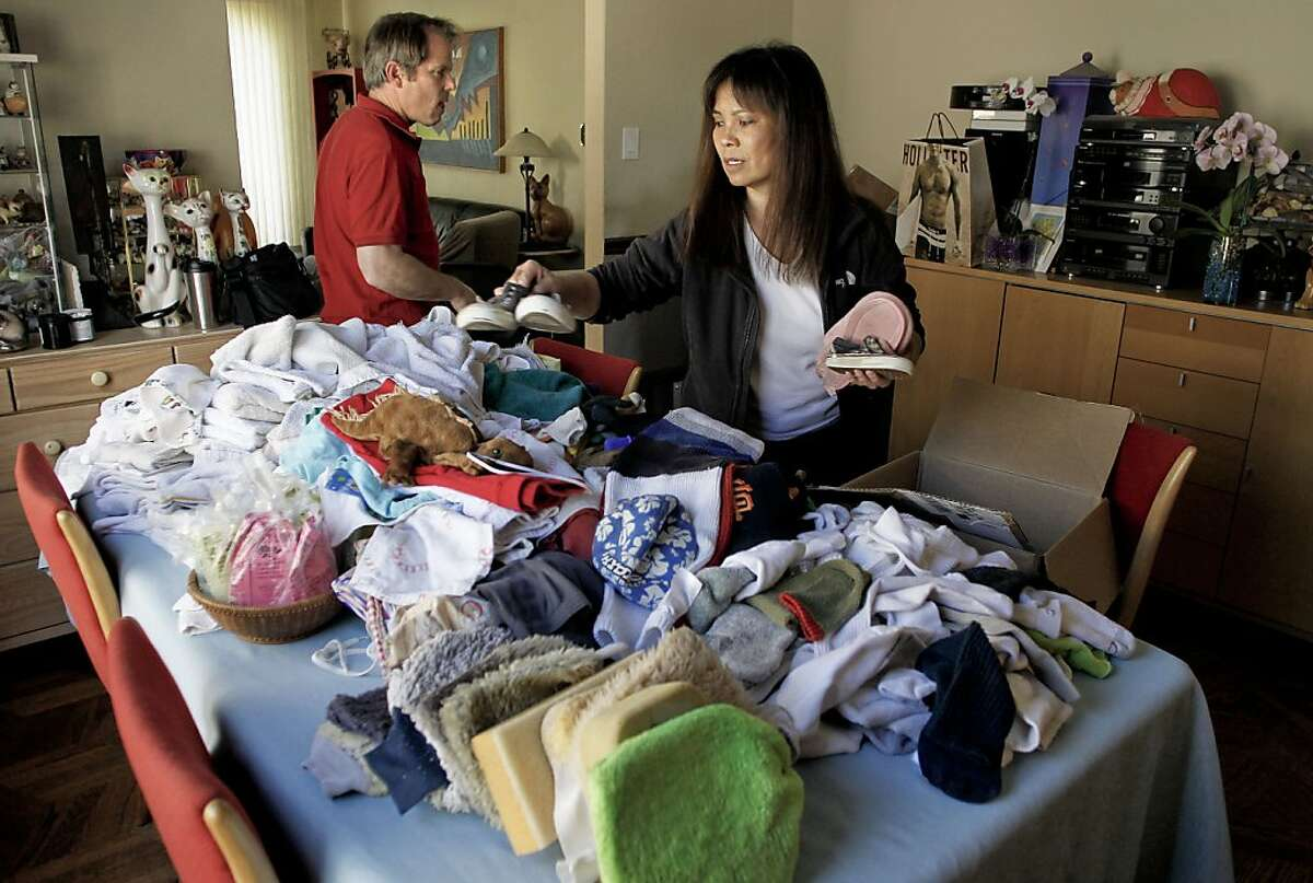 """Jim Coleman and his wife Jean Chu, the owners of """"Dusty"""", stack piles of items on Friday June 17, 2011, that their cat has brought home over the years to their house in San Mateo, Ca. """"Dusty"""" the cat has a habit of stealing and his owners have more than 600 items the cat has acquired over the past three years, including, towels, shoes, bras, hats and many more items."""
