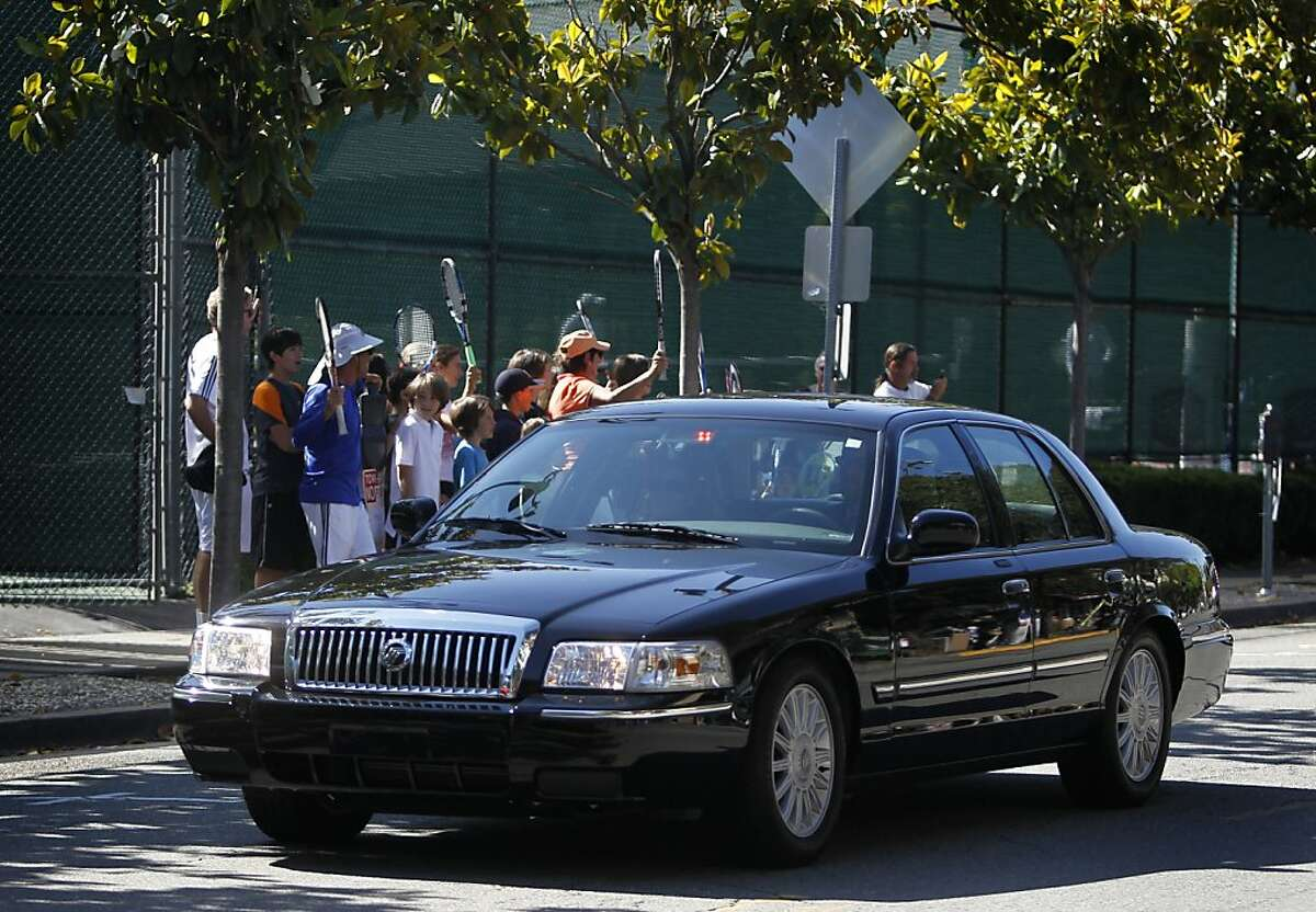 Tennis players wave to cars travelling in First Lady Michelle Obama's motorcade as she arrives at the Claremont Hotel for a breakfast fundraiser in Berkeley, Calif. on Tuesday, June 14, 2011.