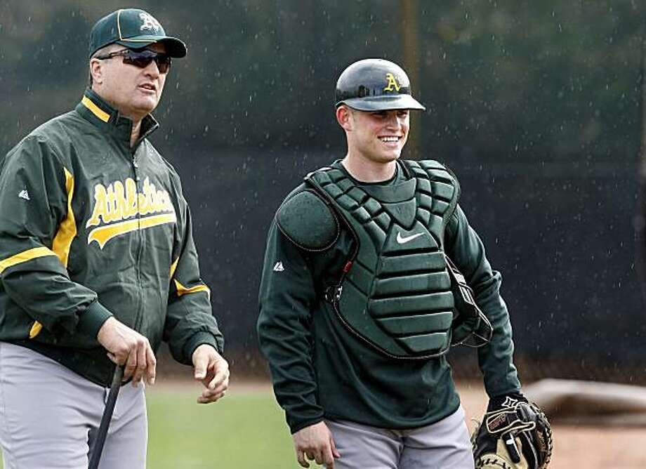 Oakland Athletics manager Bob Geren, left, gets young catcher Matt Stassi smiling on the first day of practice Sunday at spring training. Photo: Brant Ward, The Chronicle