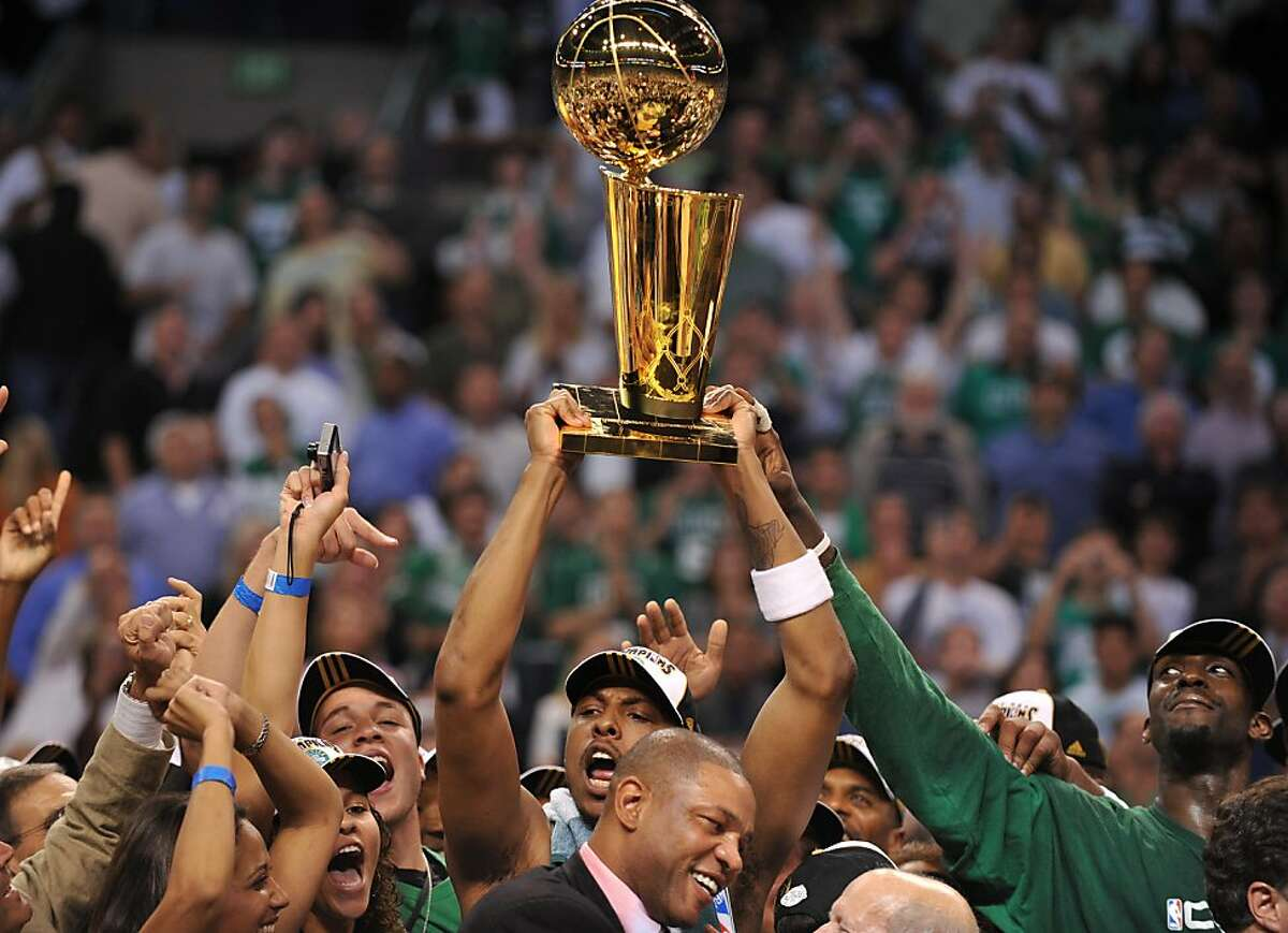 Boston Celtics' Paul Pierce (C) holds the NBA trophy with teammate Kevin Garnett (R) before head coach Doc Rivers (1rst row) after winning Game 6 of the 2008 NBA Finals, in Boston, Massachusetts, June 17, 2008. The Boston Celtics captured the National Basketball Association championship, routing the Los Angeles Lakers 131-92 to win the best-of-seven NBA Finals four games to two.