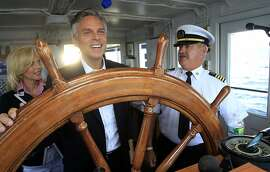 Capt. Leo O'Connell watches as possible 2012 presidential hopeful, former Republican Gov. Jon Huntsman, Jr., of Utah pilots the MS Mount Washington on Lake Winnipeasukee during a Belknap County Republican Committee cruise, Friday, June 3, 2011 in Laconia,N.H.