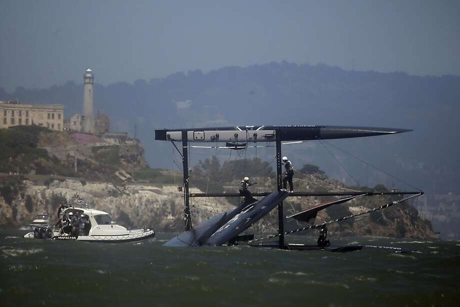 Oracle racing members work to bring their boat into an upright position after Oracle Racing AC45 Russell Coutts (5) capsized while practicing match racing against Oracle Racing AC45 James Spithill (4) (not shown) on Monday, June 13, 2011 in San Francisco, Calif. Photo: Lea Suzuki, The Chronicle