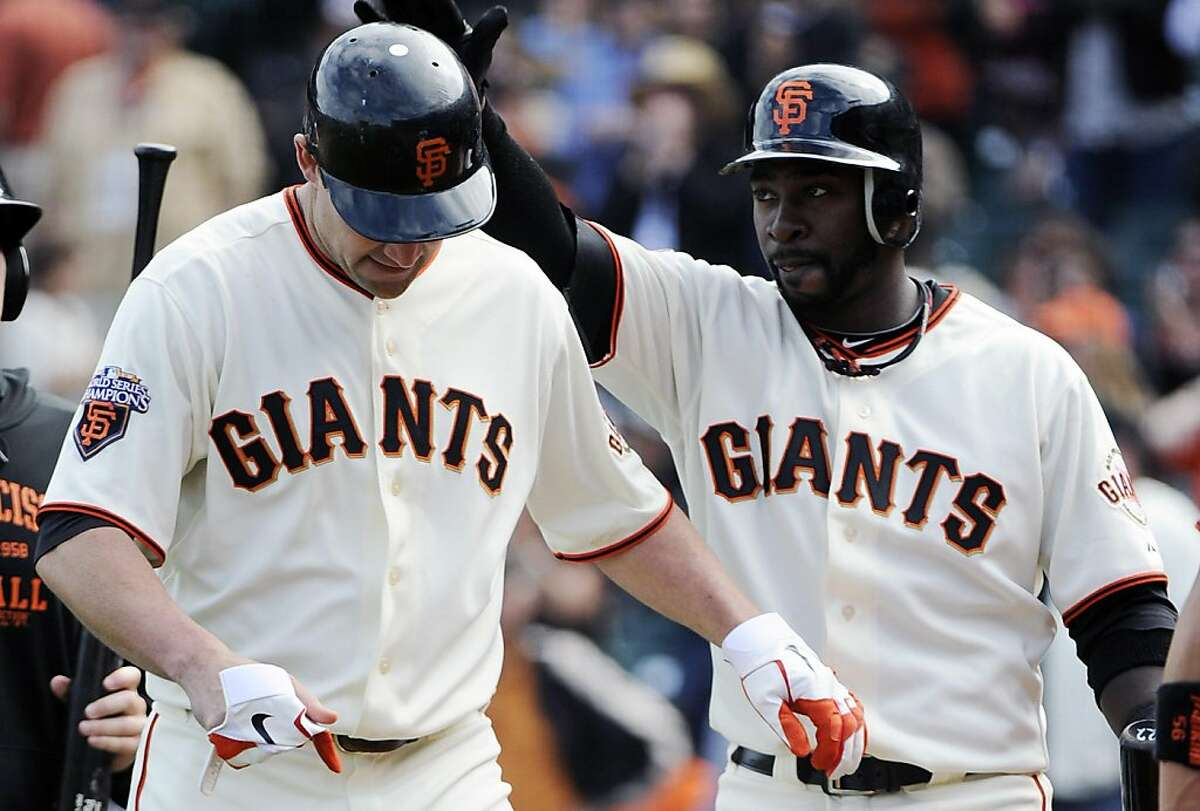 Pat Burrell #5 (L) of the San Francisco Giants is slapped on the helmet by teammate Bill Hall #29 (R) after Burrell hit a two run home run in the bottom of the ninth inning against the Cincinnati Reds during a MLB baseball game June 11, 2011 at AT&T Park in San Francisco, California. The Red won the game 10-2.