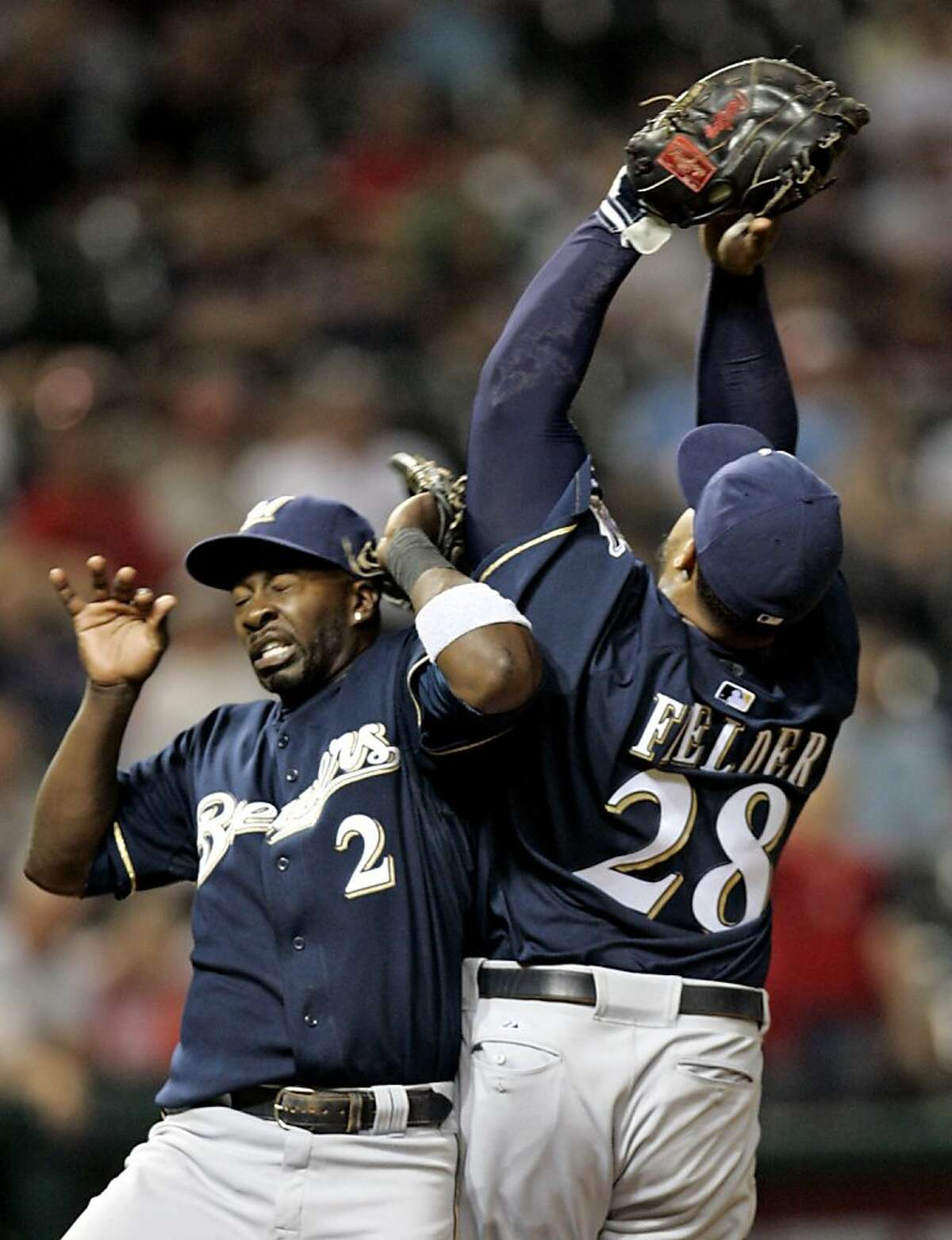 Milwaukee Brewers third baseman Bill Hall (2) and first baseman Prince Fielder (28) collide going after a ball hit by Cleveland Indians' Kelly Shoppach in the eighth inning of a baseball game Wednesday, June 17, 2009, in Cleveland. Fielder caught the ball for the out.
