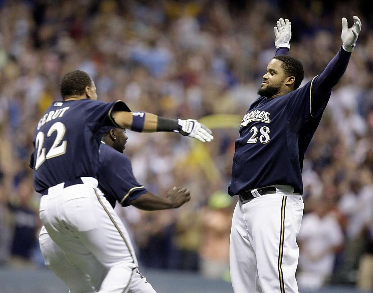 Milwaukee Brewers' Prince Fielder (28) waits to get congratulated by teammates Jody Gerut (22) and Bill Hall after hitting a game-winning hit during the ninth inning of a baseball game against the San Francisco Giants Saturday, June 27, 2009, in Milwaukee. The Brewers won 7-6.