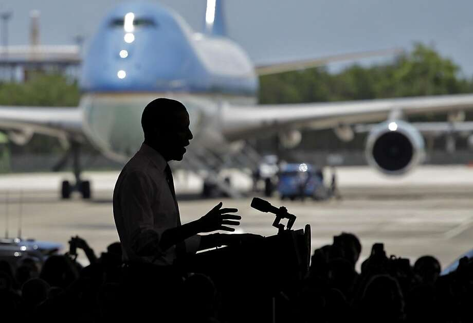 With Air Force One visible in the background, President Barack Obama speaks to a crowd gathered inside a hangar at Muniz Air National Guard Base, shortly after his arrival in San Juan, Puerto Rico, Tuesday June 14, 2011. Obama's visit to Puerto Rico marksthe first by a sitting U.S. President since John F. Kennedy. Photo: Brennan Linsley, AP