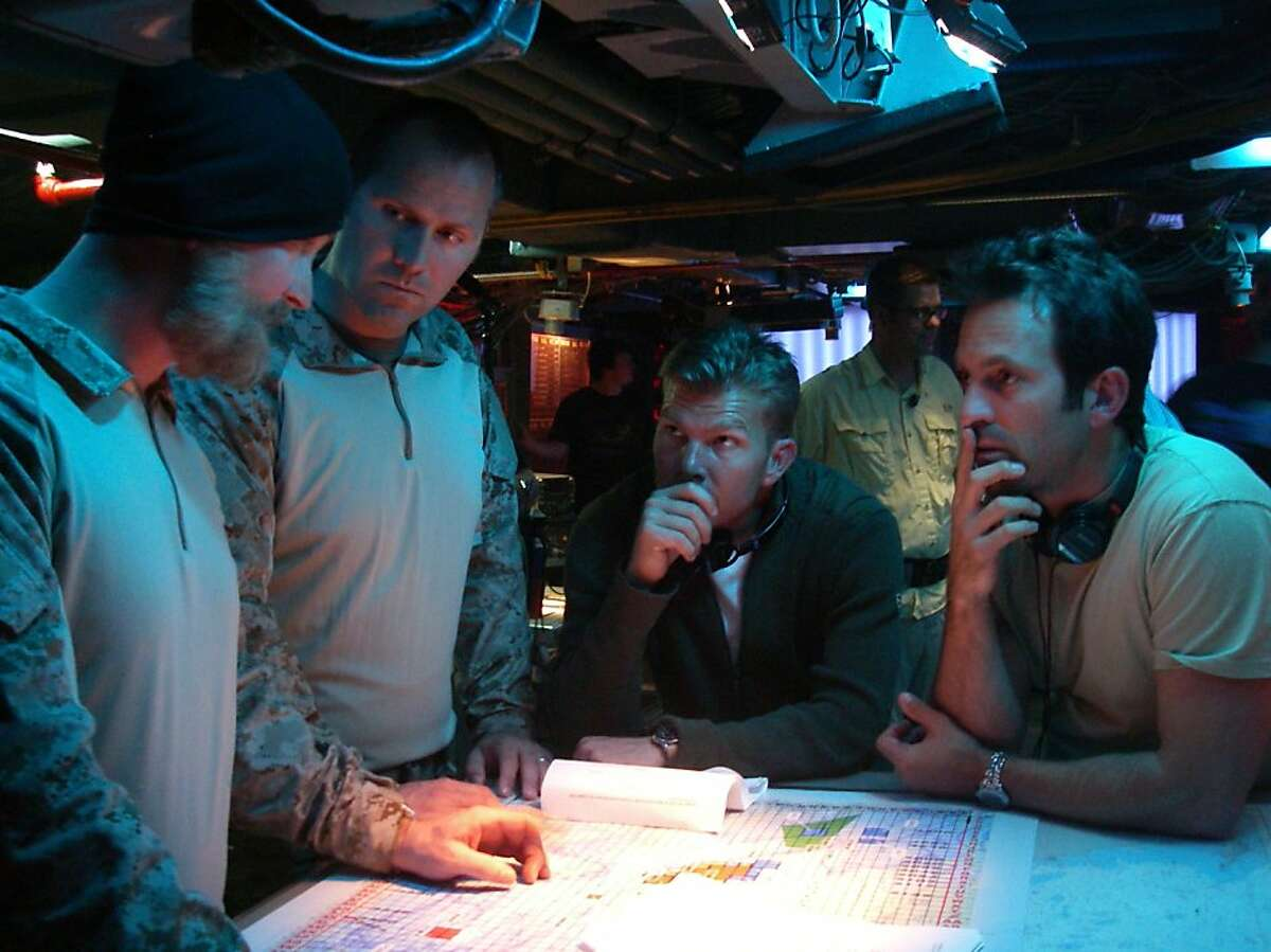 """An unnamed SEAL and the SEAL """"Rorke"""" confer with Bandito Brothers producers/directors Mike """"Mouse"""" McCoy and and Scott Waugh on the set of """"Act of Valor"""" - in this case - the bridge of the aircraft carrier Midway, moored in San Diego."""