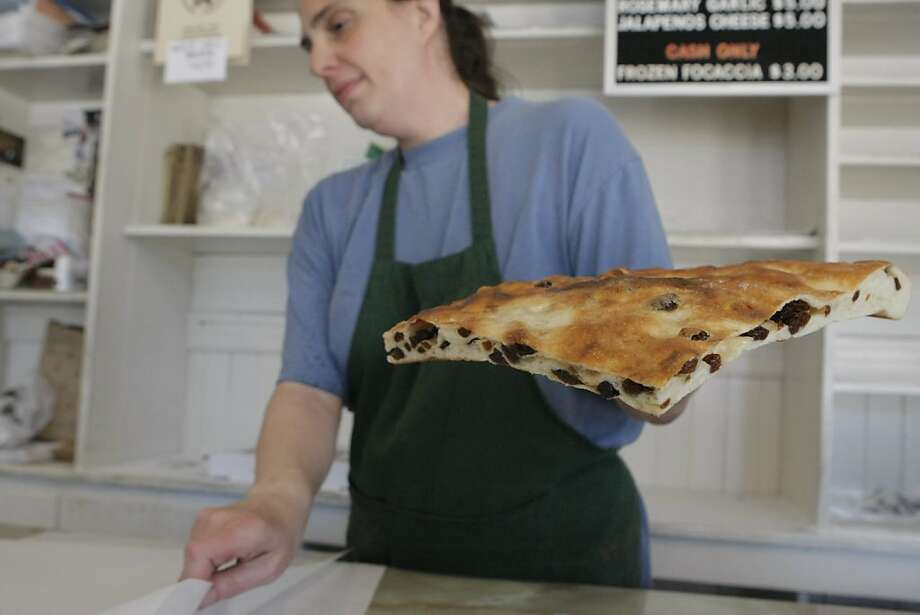Mary Sorracco prepares to wrap up a piece of raisin focaccia for a customer at Liguria Bakery in San Francisco Calif. on Thursday, June 9, 2011. Sorracco and her brothers are part of the third generation to work and run the bakery, which is celebrating 100 years of bread-making this year. Photo: Audrey Whitmeyer-Weathers, The Chronicle