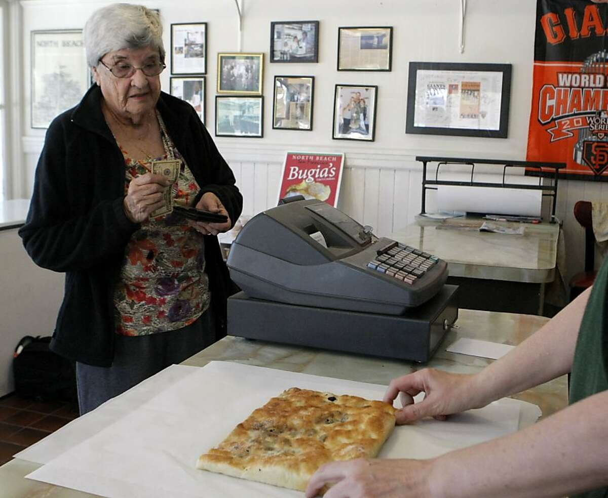 Marybelle Lukins of Santa Cruz watches as Mary Sorracco of Liguria Bakery wraps her a piece of raisin fococcia bread in San Francisco, Calif. on Thursday, June 9, 2011. Lukins said she never visits her friend without coming to Liguria Bakery to get a piece of their handmade fococcia. The bakery is celebrating 100 years of bread-making excellence this year.