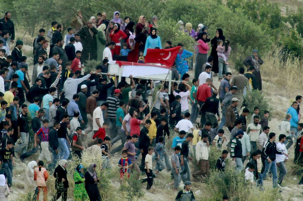 Syrians carry the coffin of an anti-regime protester on the Syrian side of the Syria-Turkey border, near the Turkish village of Guvecci in Hatay, on June 11, 2011. The protestor was killed by police gun fire during an anti-government demonstration in Jisral-Shugur, Syria on June 10. Around 4,600 Syrians have fled a brutal crackdown against pro-democracy protesters and are staying in camps in southern Turkey, a government official in Ankara told AFP Saturday.