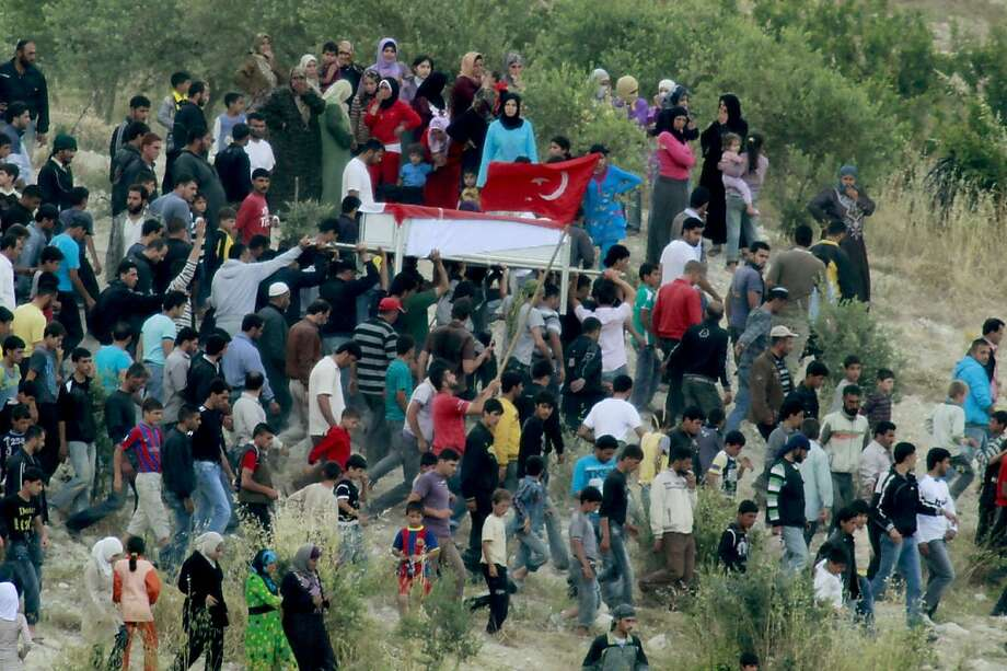 Syrians carry the coffin of an anti-regime protester on the Syrian side of the Syria-Turkey border, near the Turkish village of Guvecci in Hatay, on June 11, 2011. The protestor was killed by police gun fire during an anti-government demonstration in Jisral-Shugur, Syria on June 10. Around 4,600 Syrians have fled a brutal crackdown against pro-democracy protesters and are staying in camps in southern Turkey, a government official in Ankara told AFP Saturday. Photo: Str, AFP/Getty Images