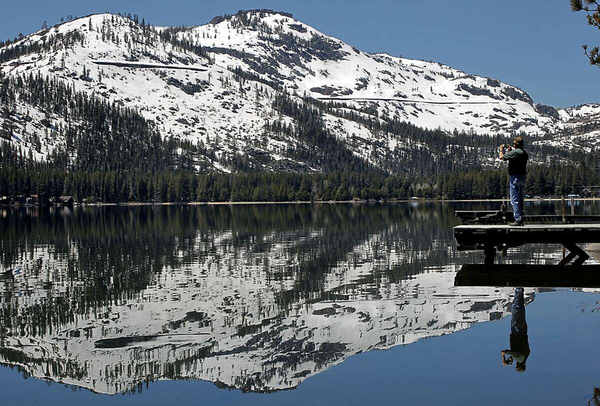 A passer by stops to photograph the late season snow that still covers Donner Peak at Donner Lake, Ca., on Tuesday June 7, 2011. The amount of snow along the Sierra Nevada Mountain Range is the deepest ever recorded this late in the year dating back to the construction of the Transcontinental Railroad starting in 1868.
