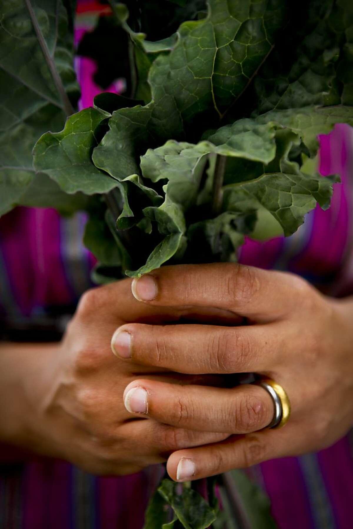 Esperanza Pallana holds freshly picked kale in her Oakland, Calif., backyard on Friday, June 3, 2011.