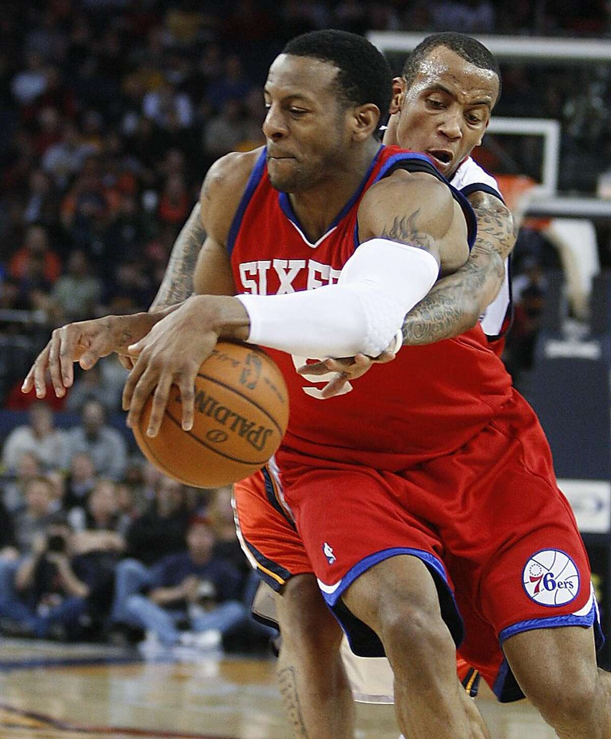 Philadelphia 76ers' Andre Iguodala (9) drives away from Golden State Warriors' Monta Ellis during the first half of an NBA basketball game Tuesday, Feb. 23, 2010, in Oakland, Calif.