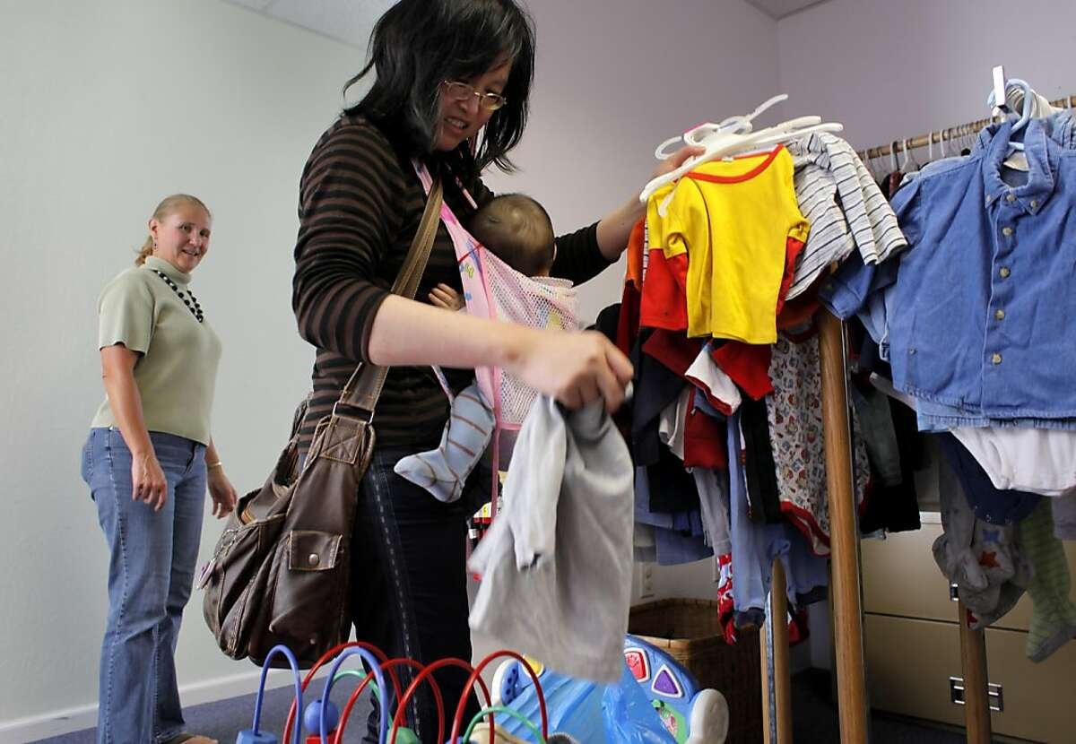 Alpha Pregnancy Center volunteer Suzanne Morris watches as a client gathers clothing for her baby.