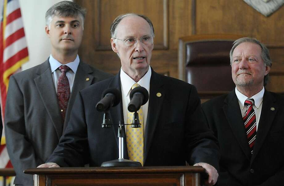 Alabama Gov. Robert Bentley sAlabama Gov. Robert Bentley is flanked by Sen. Scott Beason, R-Gardendale, left, and Micky Hammon, R-Decatur, right, as he speaks before signing into law what critics and supporters are calling the strongest bill in the nationcracking down on illegal immigration, on Thursday June 9, 2011 at the state Capitol in Montgomery, Ala. The bill  allows police to arrest anyone suspected of being an illegal immigrant if they're stopped for any other reason. It also requires public schools to determine students' immigration status and makes it a crime to knowingly give an illegal immigrant a ride. Photo: Mickey Welsh, AP