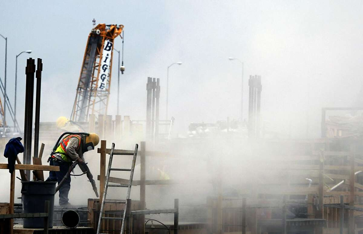A construction worker sand blasts the temporary bypass at Treasure Island.