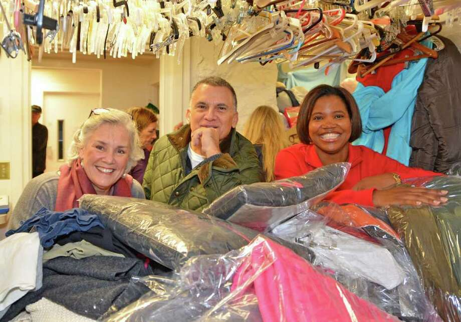 Ceci Maher, Executive Director of Person-to-Person in Darien, Frank Policastro, owner of Crescent Cleaners, and Stamford realtor Kimberly Tapscott, all lean on top of the nearly 200 coats that Ms. Tapscott collected for  the Person-to-Person coat drive.  Crescent Cleaners donated cleaning services to the collaborative effort, Wednesday morning, December 7, 2011. Photo: Jeanna Petersen Shepard