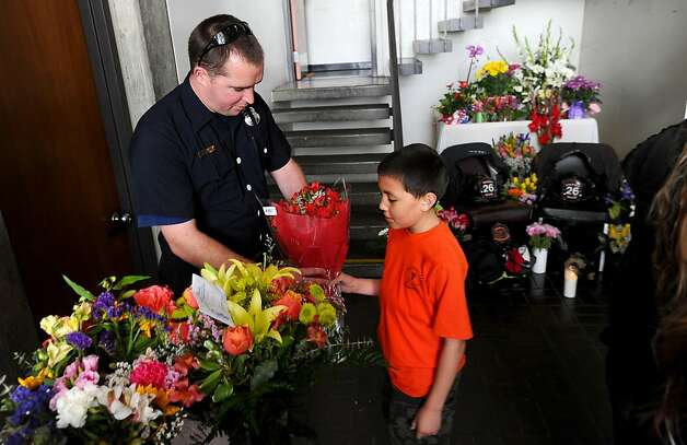 Ryan Farmer, 9, delivers flowers to fire station 26 on Sunday, June 5, 2011, in San Francisco. Farmer's uncle, a firefighter with another station, discovered the bodies of two fallen firefighters during last week's blaze in Diamond Heights, said his father. Photo: Noah Berger, Special To The Chronicle