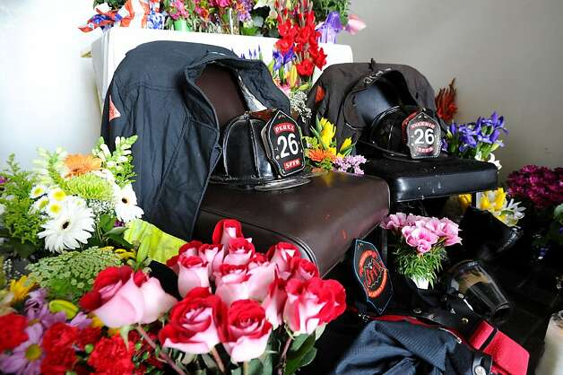 Turnout gear for deceased firefighters Anthony Valerio and Lt. Vincent Perez sit surrounded by flowers at fire station 26 on Sunday, June 5, 2011, in San Francisco. Photo: Noah Berger, Special To The Chronicle