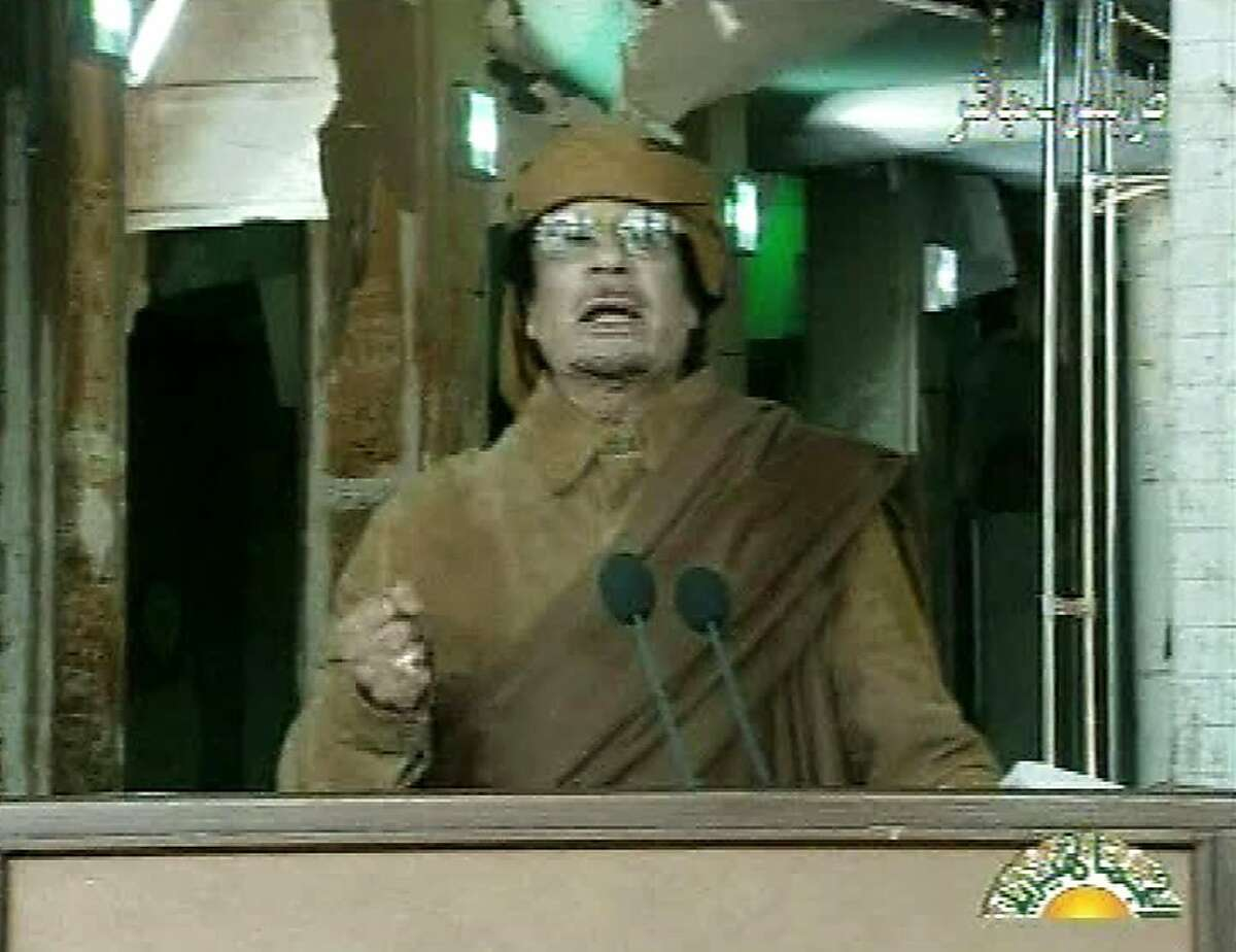 This image broadcast on Libyan state television Tuesday, Feb. 22, 2011, shows Libyan leader Moammar Gadhafi as he addresses the nation in Tripoli, Libya. Libya's Gadhafi vowed to fight on against protesters demanding his ouster and die as martyr.