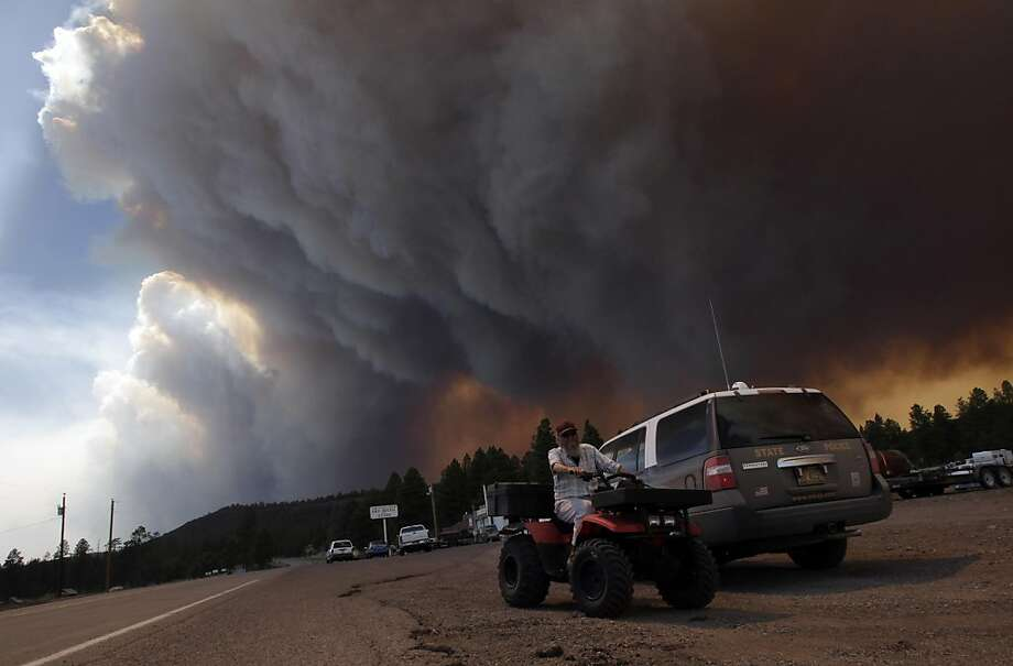 Robert Joseph, 64, rides his ATV as smoke plumes from the Wallow fire fill the sky in Luna, N.M., Monday, June 6, 2011. Firefighters worked furiously Monday to save a line of mountain communities in eastern Arizona from a gigantic blaze that has forced thousands of people from their homes and cast a smoky haze over states as far away as Iowa. Photo: Jae C. Hong, AP
