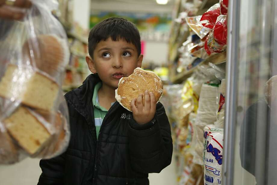 Benjamin Serratos eats a piece of Pan Dulce (Mexican sweet bread) while shopping with his mother at the Arabic owned Mi Ranchito Produce and Carniceria in San Francisco Calif, on Friday, May 27, 2011. Photo: Alex Washburn, The Chronicle