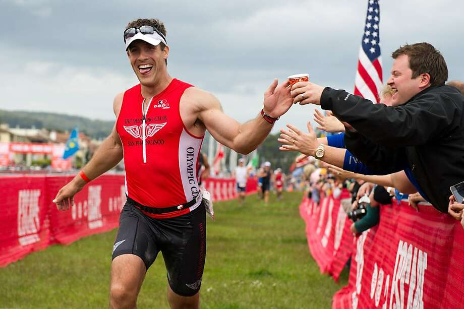 Brian Hassan of San Francisco high fives Justin Roberts (right) as he runs down to the finish line during the 31st Annual Escape from Alcatraz Triathlon on June 5, 2011 in San Francisco, Calif.  Photograph by David Paul Morris/Special to the Chronicle Photo: David Paul Morris, Special To The Chronicle