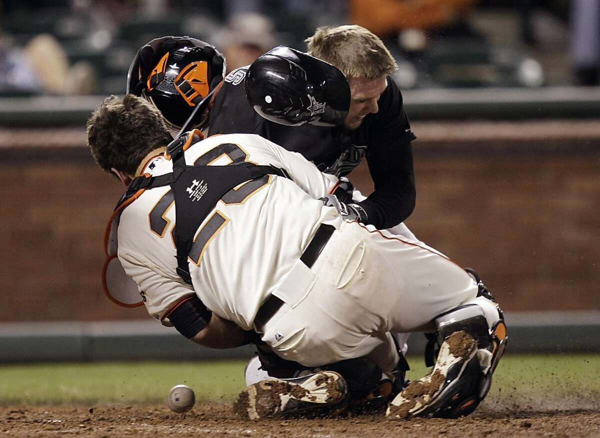 Florida Marlins' Scott Cousins, top, collides with San Francisco Giants catcher Buster Posey (28) on a fly ball from Emilio Bonifacio during the 12th inning of a baseball game in San Francisco, Wednesday, May 25, 2011. Cousins was safe for the go ahead run and Florida won 7-6.