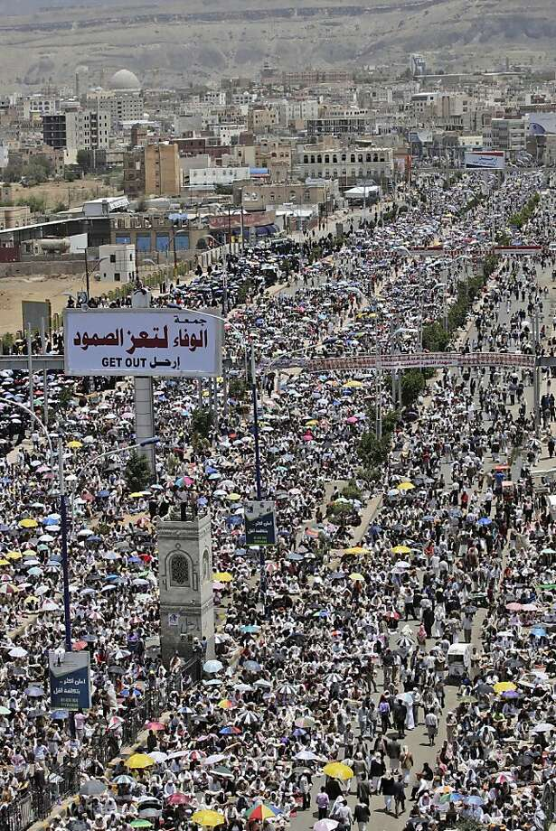 "Anti-government protestors, attend a demonstration demanding the resignation of Yemeni President Ali Abdullah Saleh, in Sanaa, Yemen, Friday, June 3, 2011. A government official says Yemen's president was lightly injured and four top officials wounded when opposition tribesmen struck his palace with rockets. Billboard center reads in arabic, "" Loyal for Taiz"". Photo: Hani Mohammed, AP"