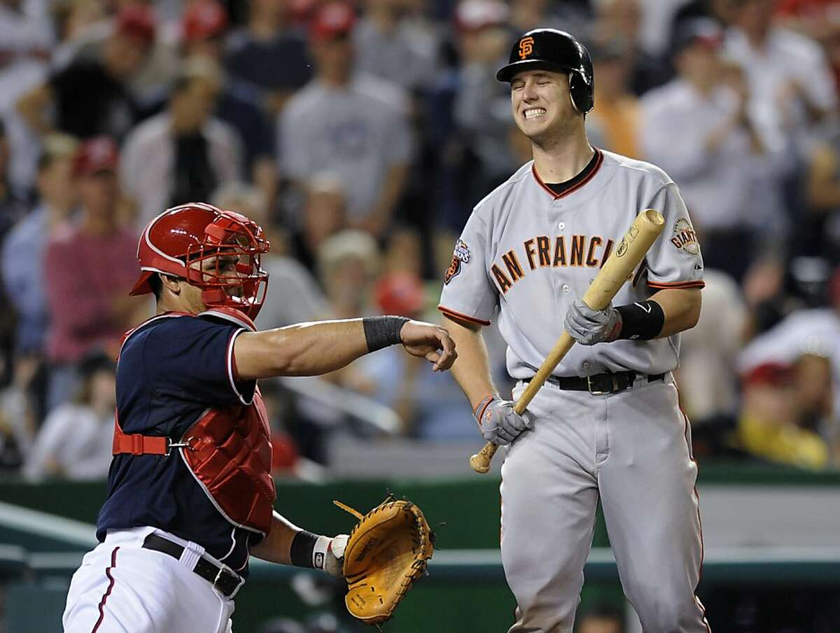 San Francisco Giants' Buster Posey, right, reacts as he bats during the ninth inning of a baseball game, as Washington Nationals catcher Wilson Ramos returns the ball to the pitcher, Monday, May 2, 2011, in Washington. The Nationals won 2-0.