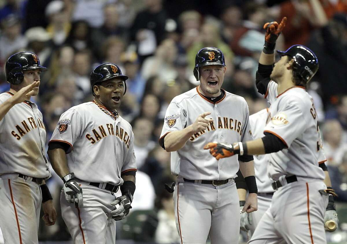 San Francisco Giants' Brandon Crawford, right, points to the sky as he celebrates with teammates, from left to right, Nate Schierholtz, Miguel Tejada and Aubrey Huff after all four scored on Crawford's grand slam during the seventh inning of a baseball game against the Milwaukee Brewers Friday, May 27, 2011, in Milwaukee.