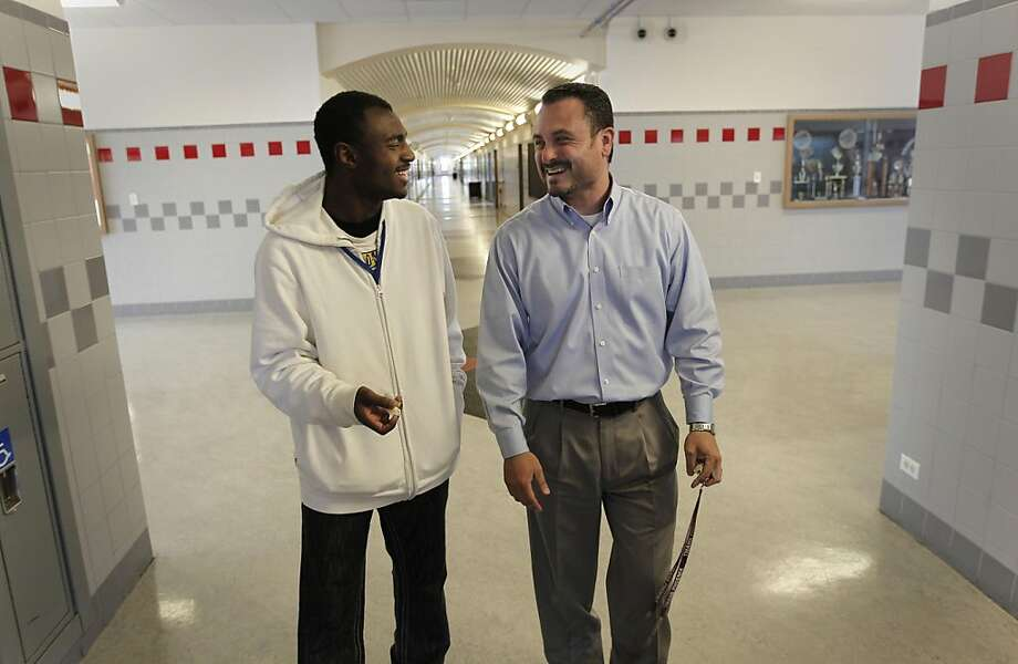 Evander Williams walks the halls of his old school with principal, Guillermo Morales on Thursday June 2, 2011. Williams, a recent graduate of Thurgood Marshall High School in San Francisco, Ca., faced street violence, the murder of friends, bullying and more. He credits his success to the Thurgood Marshall Wellness Program which gave him advice and guidance through his school years and is now set to move onto college. Photo: Michael Macor, The Chronicle