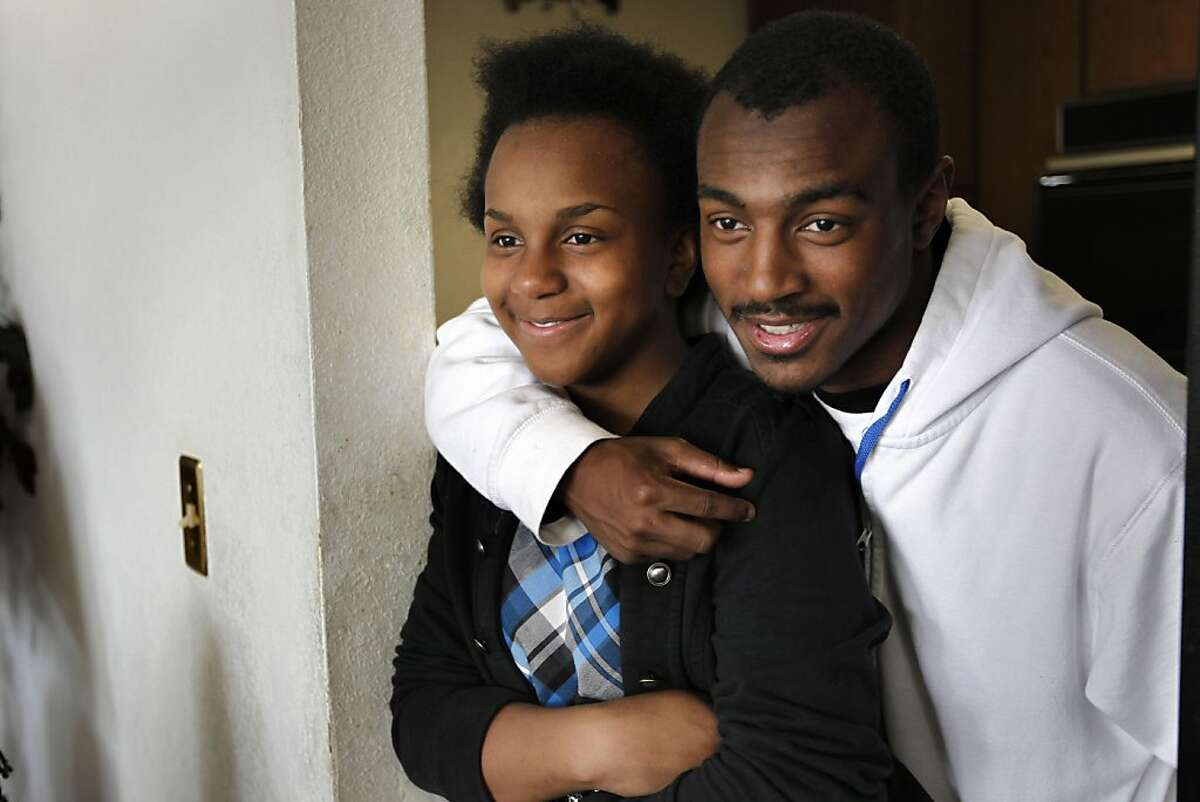 Evander Williams with his 11-year-old sister Chy'Enne at their Hunters Point home in San Francisco, Ca. on Thursday June 2, 2011. Williams is a recent graduate of Thurgood Marshall High School in the Bay View neighborhood. Williams faced street violence, the murder of friends, bullying and more. He credits his success to the Thurgood Marshall Wellness Program which gave him advice and guidance through his school years and is now set to move onto college.