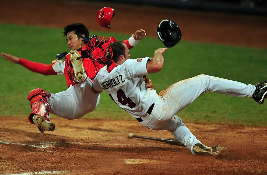 Nate Schierholtz (R) of the US barrells into Chinese catcher Yang Yang (L) to score off a hit by Terry Tiffee  in their men's preliminary round baseball game at the Wukesong Baseball Venue during the 2008 Beijing Olympic Games on August 18, 2008. The US won 9-1. Photo: Frederic J. Brown, AFP / Getty Images