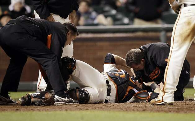 San Francisco Giants catcher Buster Posey (28) is tended by trainers after a collision with Florida Marlins' Scott Cousins on a fly ball from Emilio Bonifacio during the 12th inning of a baseball game in San Francisco, Wednesday, May 25, 2011. Cousins wassafe for the go ahead run and Florida won 7-6. Photo: Marcio Jose Sanchez, AP