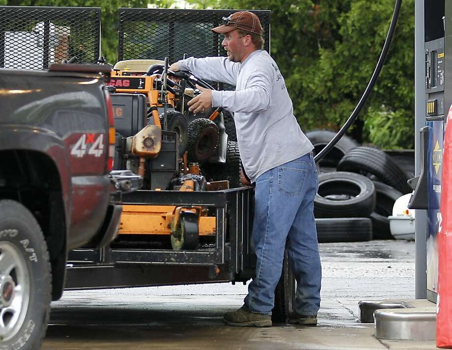A landscaper fills one of his lawn tractors with gas at the Sunoco gas station in Moreland Hills, Ohio, on Thursday, May 26, 2011. The price for a gallon for regular unleaded gasoline at the station was $3.87.9. High gasoline prices, government budget cuts and weaker-than-expected consumer spending caused the economy to grow only weakly in the first three months of the year. Photo: Amy Sancetta, AP