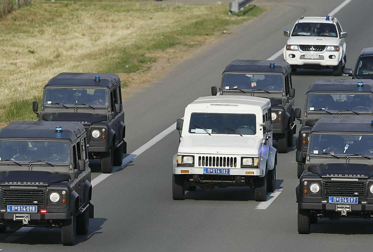 The white vehicle at centre, thought to transport war crimes suspect Ratko Mladic is surrounded by convoy vehicles as it arrives at a Belgrade International Airport, Serbia, Tuesday, May 31, 2011. War crimes suspect Ratko Mladic is on his way to The Hague, the Serbian justice minister said, just hours after judges rejected his appeal Tuesday to stop his extradition to a U.N. tribuna (AP Photo/Darko Vojinovic)
