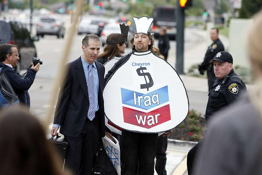 "Jeff Grubler (center left) walks alongside a ""moneybag"" during Chevron's annual shareholder meeting at Chevron Headquarters in San Ramon, on Wednesday. Grubler played the role of CEO John Watson with his ""moneybags"" for a musical protest. Photo: Thomas Levinson, The Chronicle"