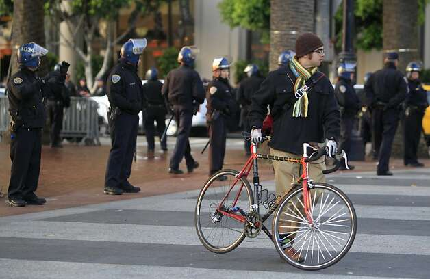 A bicyclist walks past a police line after authorities cleared out the Occupy encampment at Justin Herman Plaza in an early morning raid in San Francisco, Calif. on Wednesday, Dec. 7, 2011. Photo: Paul Chinn, The Chronicle