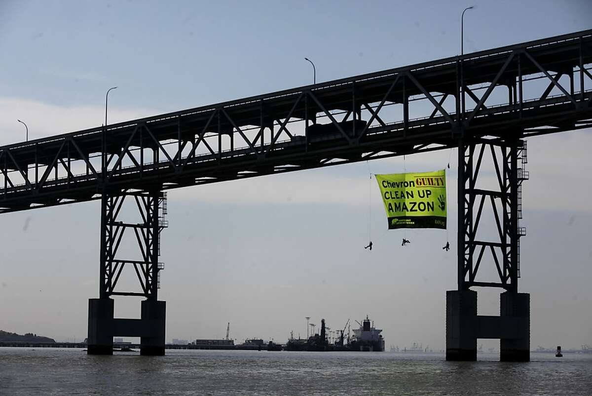 Two days before the start of the annual Chevron shareholders meeting, Thomas Cavanagh, Amanda Fiore and Matt Leonard, activists with the Rainforest Action Network drop a 30'x50' banner on the side of the Richmond San Rafael Bridge that accuses the company of wrong doing in the Amazaon, on Monday May 23, 2011 in Richmond, Calif.
