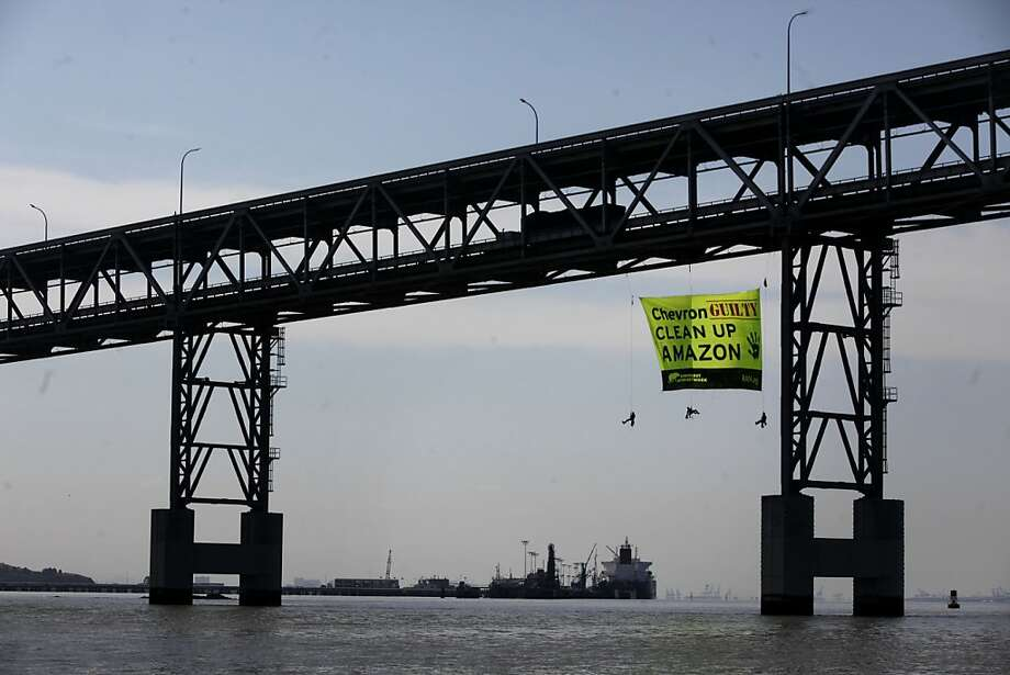 Two days before the start of the annual Chevron shareholders meeting, Thomas Cavanagh, Amanda Fiore and Matt Leonard, activists with the Rainforest Action Network drop a 30'x50' banner on the side of the Richmond San Rafael Bridge that accuses the company of wrong doing in the Amazaon, on Monday May 23, 2011 in Richmond, Calif. Photo: Mike Kepka, The Chronicle