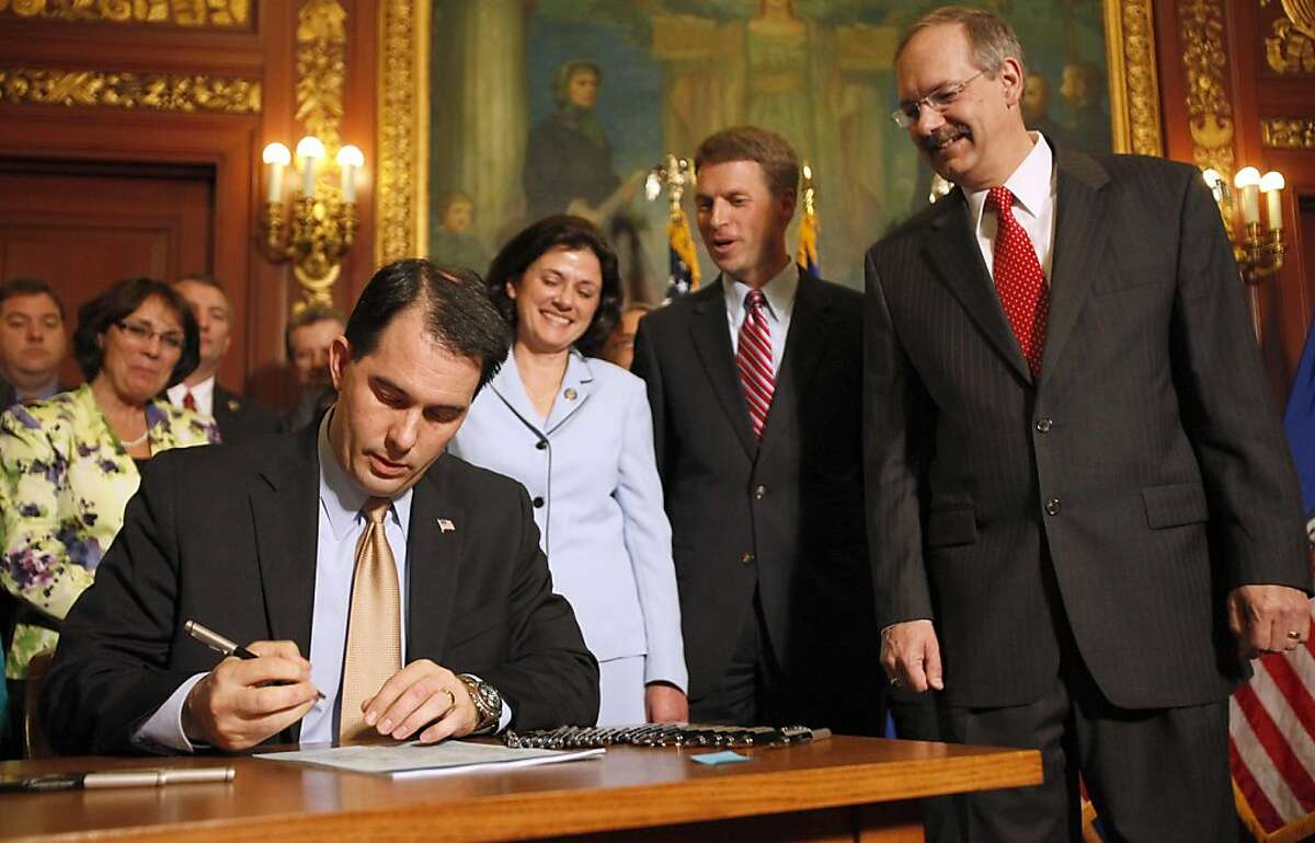 Wisconsin Gov. Scott Walker signs the Voter ID Bill into law at the state Capitol in Madison, Wis., Wednesday, May 25, 2011. The bill is a requirement that voters in Wisconsin show photo identification at the polls, marking the end of a nearly decade-longpush by Republicans to enact it.