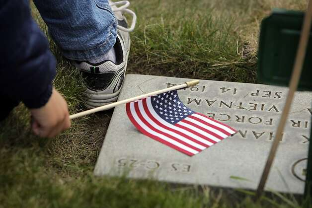 Kieran Baker, 5, holds a flag on a grave as he listens to speakers during services for Memorial Day at the San Francisco National Cemetery on Monday. Photo: Carlos Avila Gonzalez, The Chronicle
