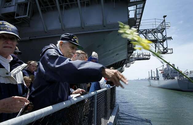 Henry Zatarain throws flowers off a deck of the USS Hornet in memory of his deceased shipmates on Memorial Day on Monday in Alameda. Photo: Brant Ward, The Chronicle