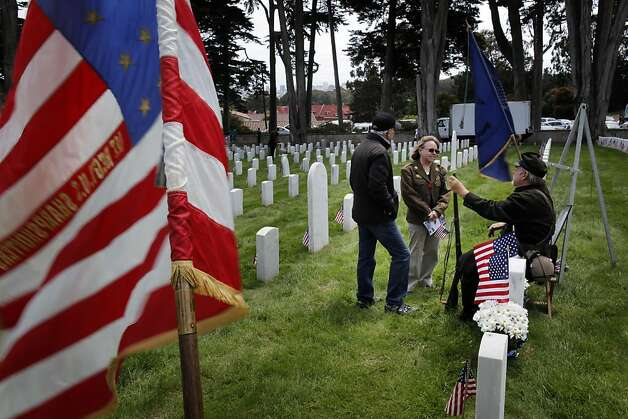 Sue and Donald Burns of San Bruno speak to Ted Stahr, seated, a Civil War re-enactor, during Memorial Day Services at the San Francisco National Cemetery on Monday. Photo: Carlos Avila Gonzalez, The Chronicle